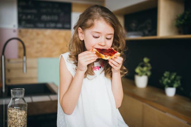 Little girl having breakfast stock photo
