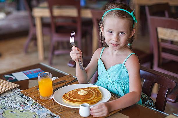Kleines Mädchen, ein Frühstück mit Saft und Pfannkuchen – Foto