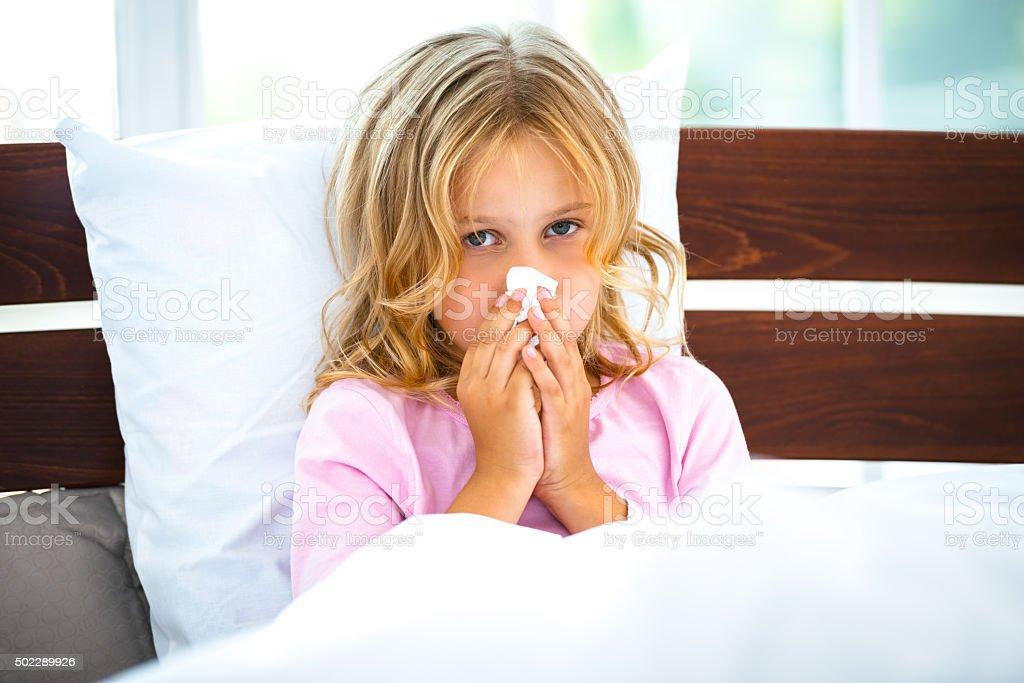 Photo of little girl sitting on white bed in morning. Girl having...