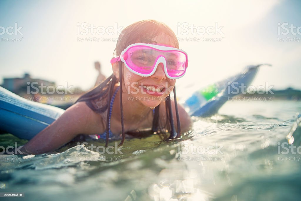 Little girl having fun at sea on air bed stock photo
