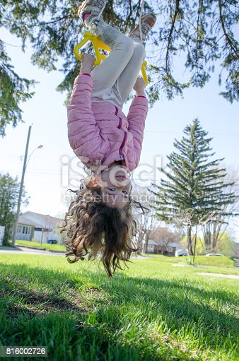 Little girl having fun while making the plane on a swing outside during a day of springtime
