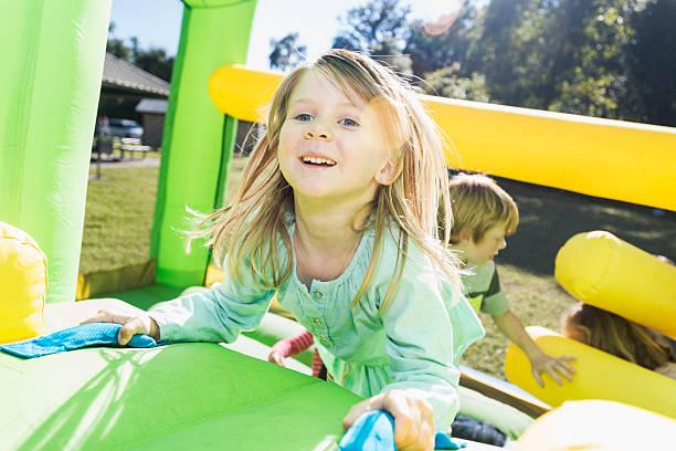 kleines mädchen mit lustigen klettermöglichkeiten auf einem bounce house - sommerfest kindergarten stock-fotos und bilder