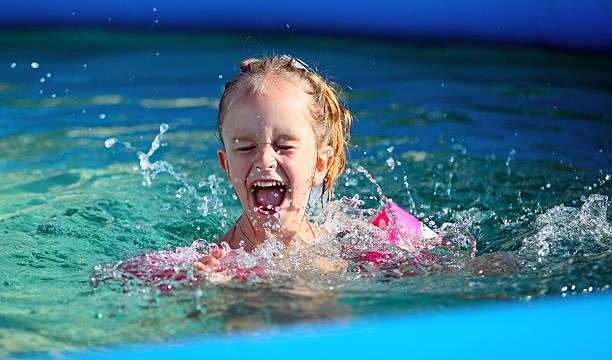 Little girl having fun in the swimming pool stock photo