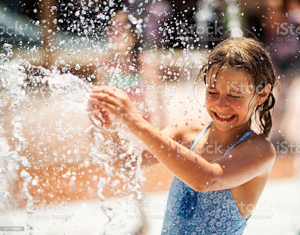 Little girl having fun in water park fountain stock photo