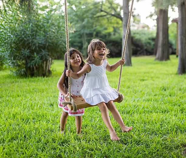 Kleine Mädchen haben Spaß auf der Schaukel im Freien – Foto