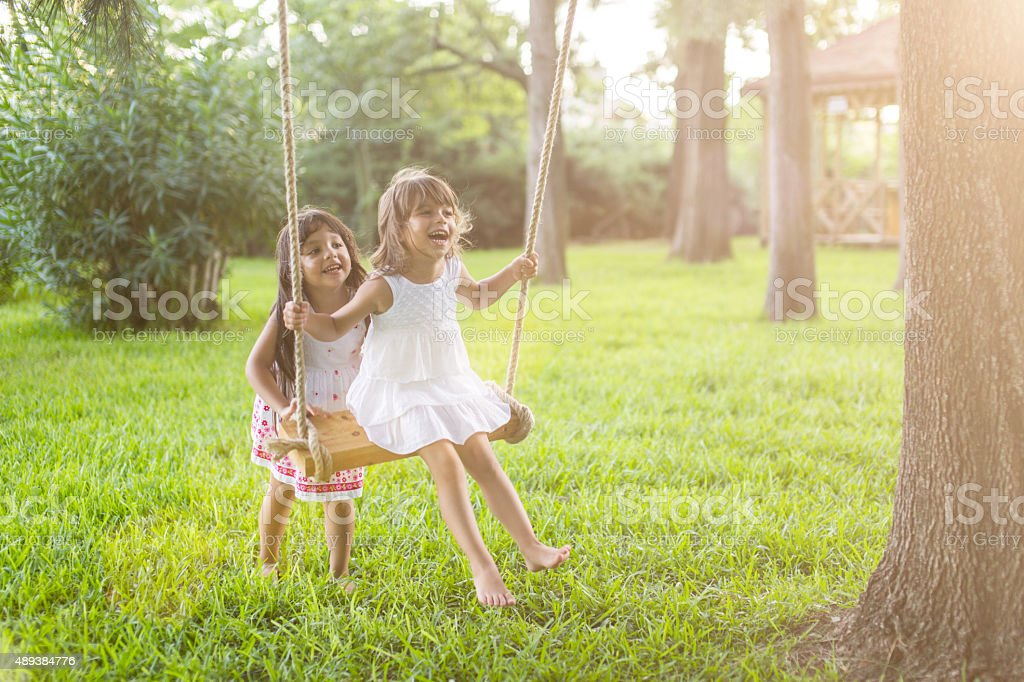 Little girl having fun on a swing outdoor stock photo