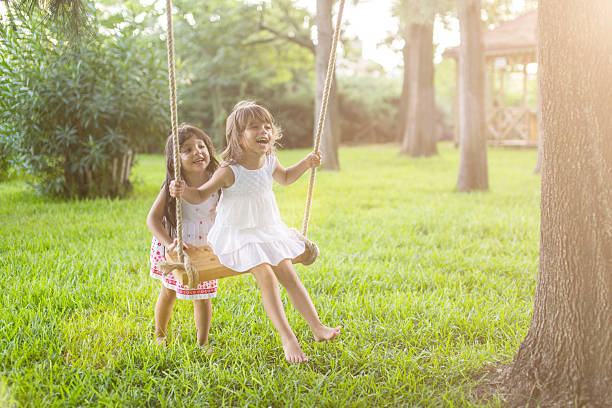Little girl having fun on a swing outdoor stock photo