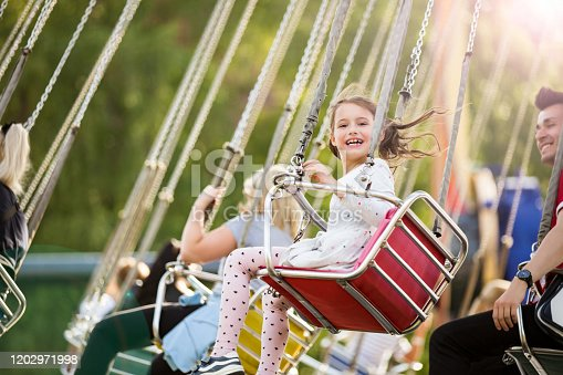 Little girl having fun on chain carousel. Happy summer memories. Carefree childhood and happiness