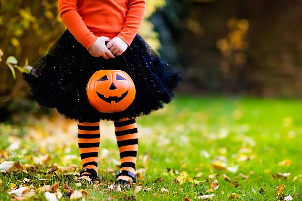 little girl having fun on halloween trick or treat - halloween fotografías e imágenes de stock
