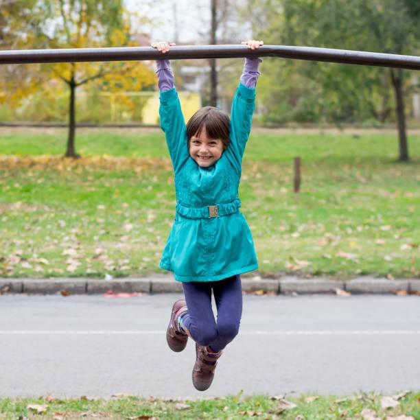 little girl having fun on playground gymnastics bar - horizontal bar stock photos and pictures