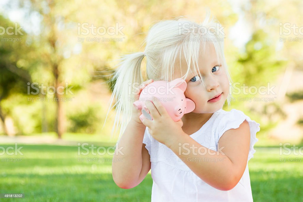 Little Girl Having Fun with Her Piggy Bank Outdoors stock photo