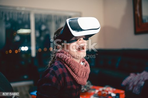 1019302738istockphoto Little Girl Having Fun with Virtual Reality Simulator and Gesturing 828154692