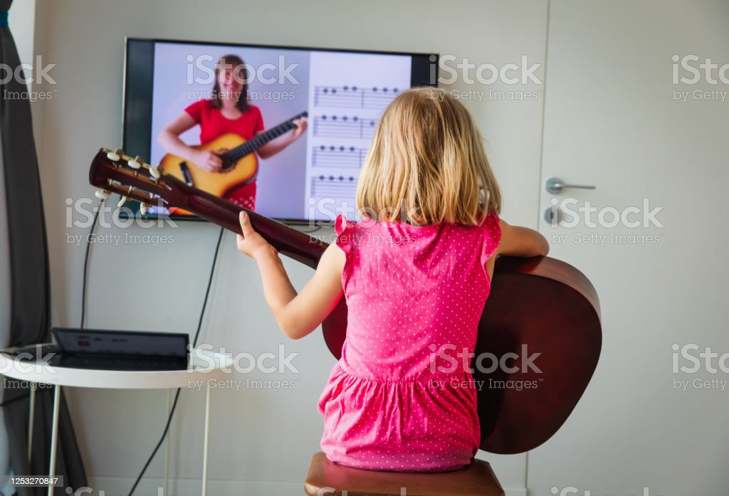 little girl having guitar lesson online at home little girl having guitar lesson online, distant learning, remote music class Acoustic Guitar Stock Photo