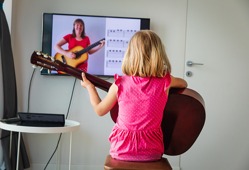 Little Girl Having Guitar Lesson Online At Home Stock Photo - Download Image Now