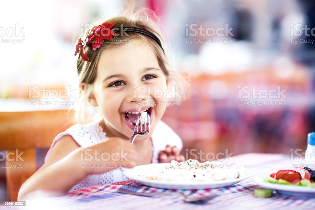 Little Girl Having Her Meal With Pleasure stock photo