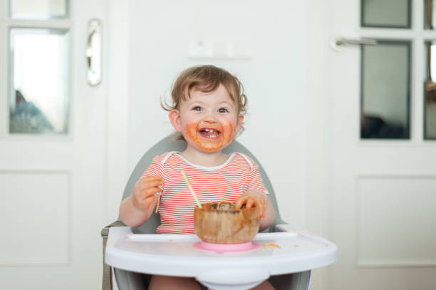 Little girl having lunch in high chair stock photo