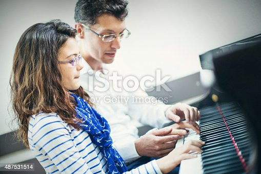 Little schoolgirl having piano class.She has long and curly brown hair. Her male teacher is sitting next to her and helping while the girl is playing. The teacher is gesturing and endorsing the girl. Side view.