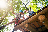 Kids working together on difficult ropes course in adventure park. Sunny summer day.\n