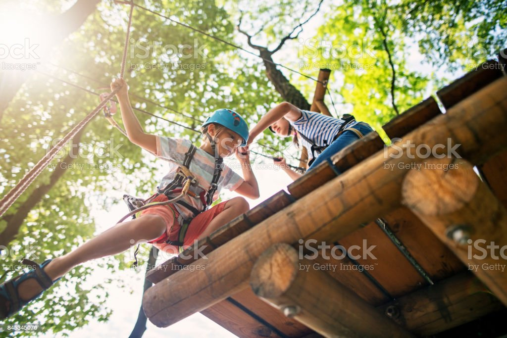 Kleines Mädchen hilft ihr Bruder am Hochseilgarten – Foto