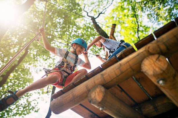 Little girl helping her brother on ropes course stock photo