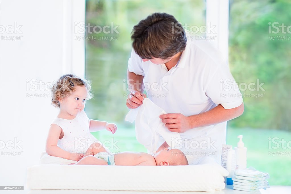 Little girl helping her father choose outfit for brother royalty-free stock photo