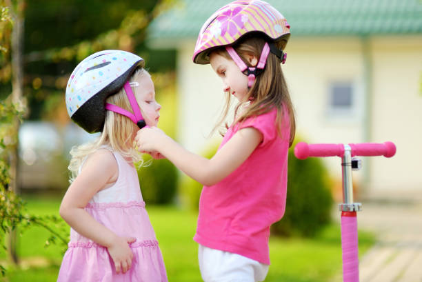 Little girl helping her sister to put a helmet on stock photo