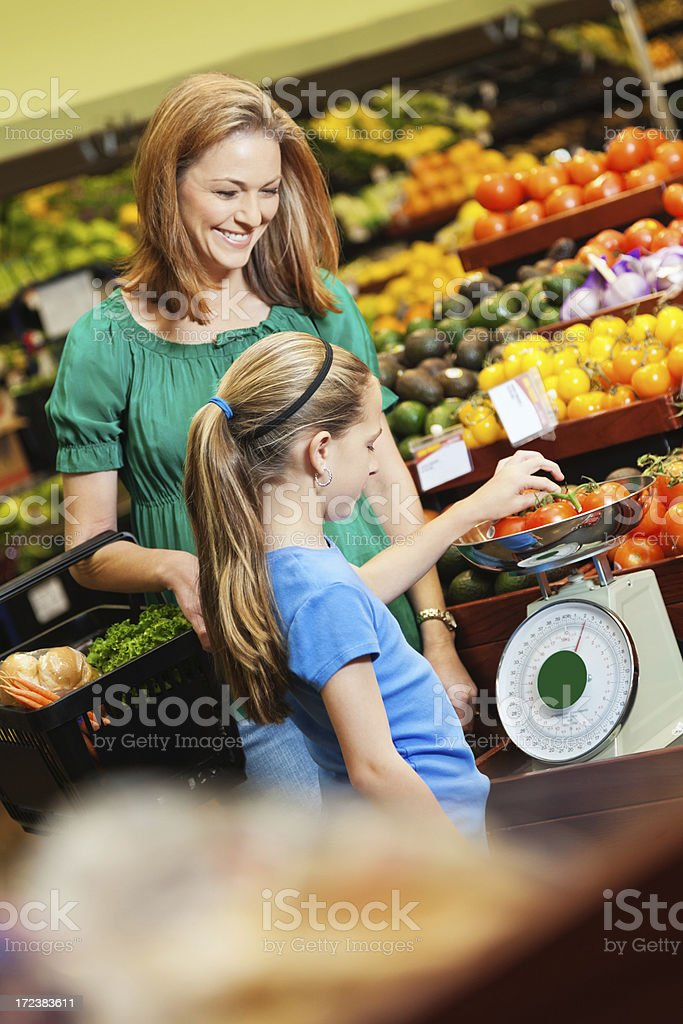 Little girl helping mom weigh produce in supermarket royalty-free stock photo