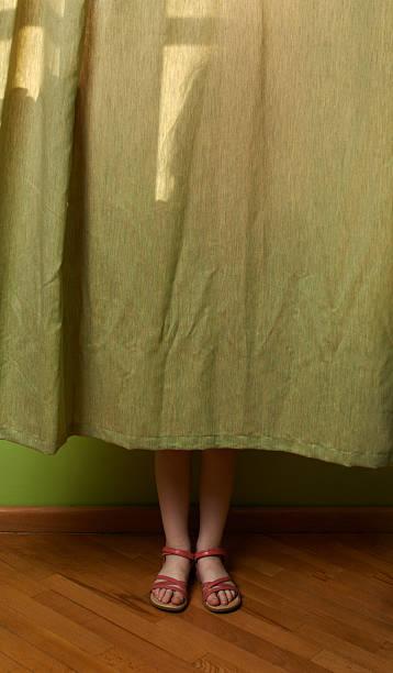 kleines mädchen versteckt hinter dem vorhang - mädchenraum vorhänge stock-fotos und bilder