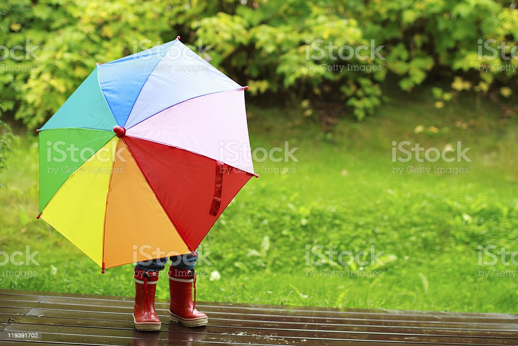 Little girl hiding behind umbrella stock photo