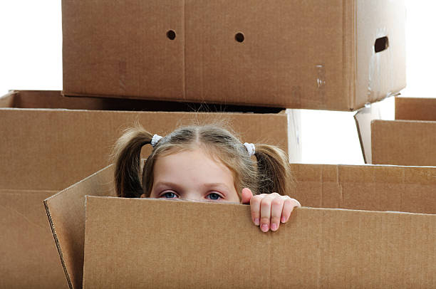 little girl hiding between boxes stock photo