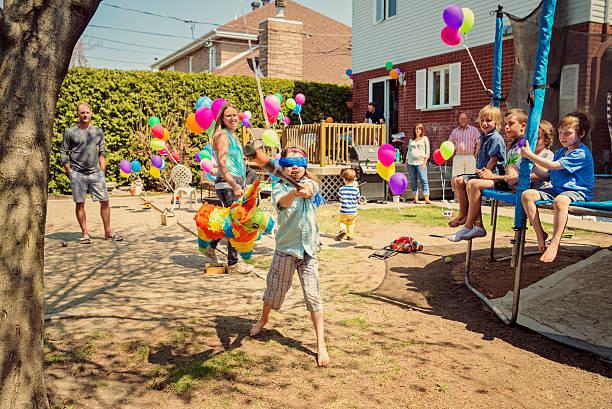 Cтоковое фото Маленькая девочка, ударяя Пиньята на день рождения в пригород заднем дворе.
