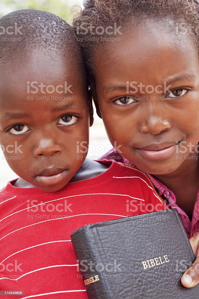 Little girl holding a bible with her brother stock photo