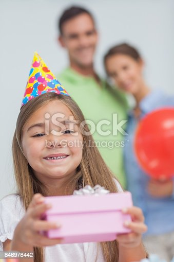 Little girl holding a birthday present during her birthday