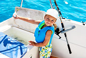 Lovely smiling little girl holding a fish. Fishing on a boat.