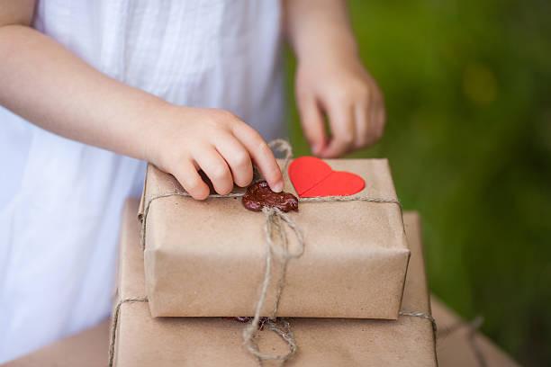 kleines mädchen halten geschenk-box, nahaufnahme. - bastelkarton stock-fotos und bilder