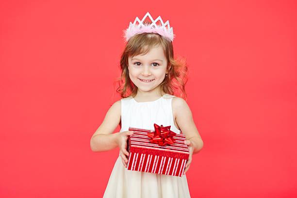 kleines mädchen hält ein geschenk box - jugendliche geburtstag geschenke stock-fotos und bilder