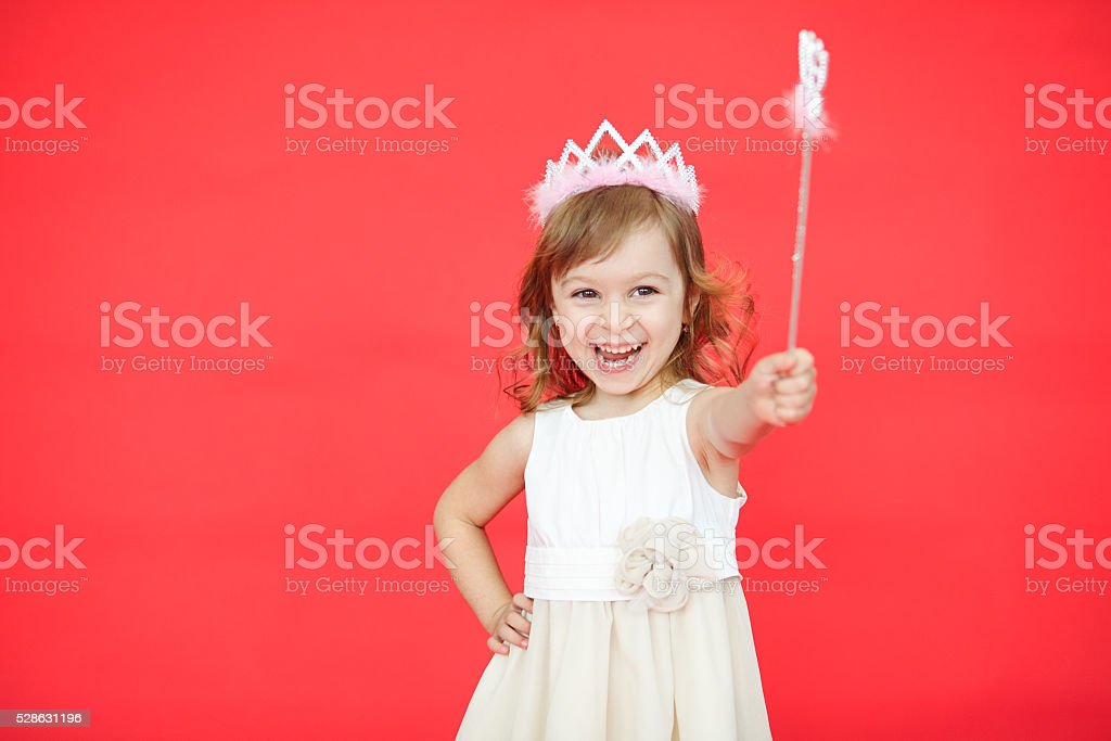 Little girl holding a magic wand in her hand stock photo