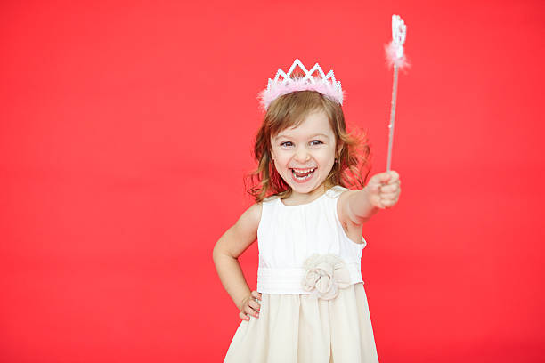 kleines mädchen halten zauberstab in der hand - prinzessin kleid kind stock-fotos und bilder