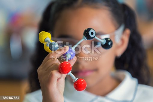 istock Little girl holding a model of molecular structure 639407584