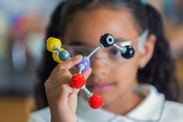 Little girl holding a model of molecular structure - foto de stock