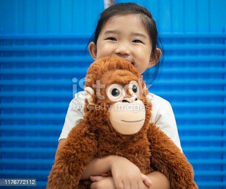 Little girl holding a orangutan plush toy