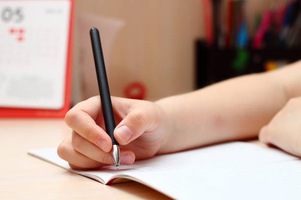A little girl holding a pen and writing in a notebook. stock photo