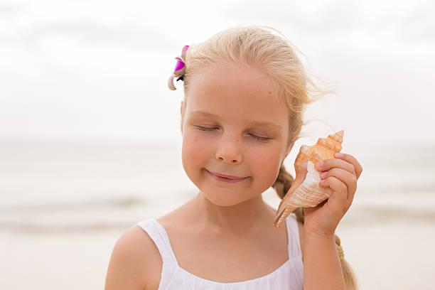little girl holding a seashell - zukunftswünsche stock-fotos und bilder