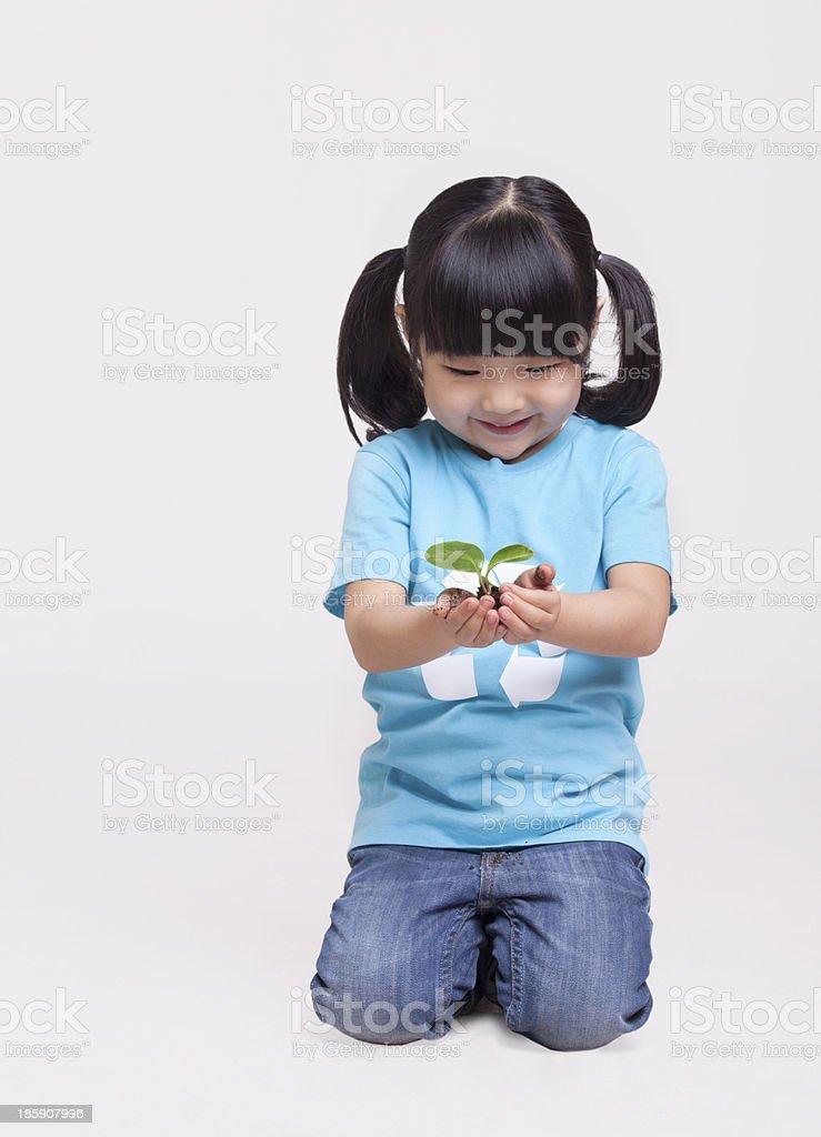 Little girl holding a seedling, studio shot royalty-free stock photo