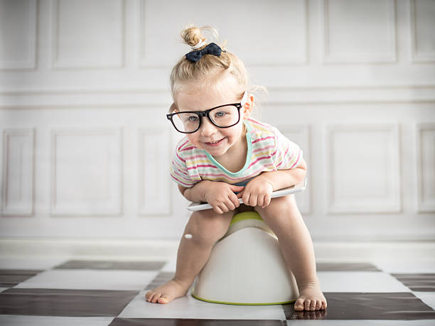 A little girl holding a tablet while sitting on white potty stock photo