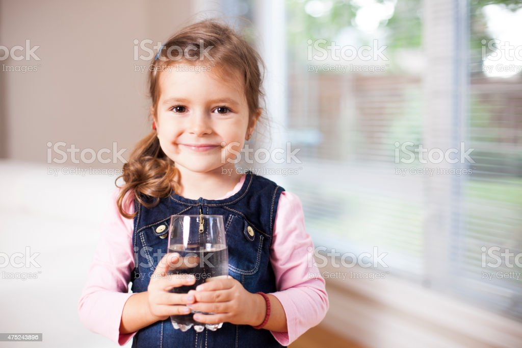 Little girl holding a water glass, looking at the camera stock photo