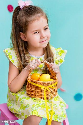 istock Little girl holding basket with yellow eggs 470873208