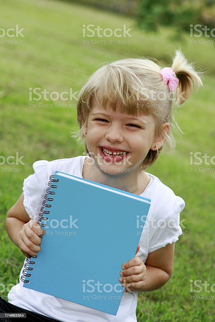 Little girl holding book outdoors royalty-free stock photo