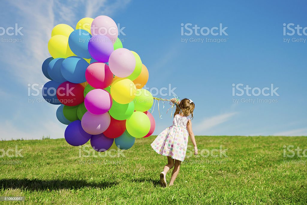 Little girl holding colorful balloons. Child playing on a green stock photo