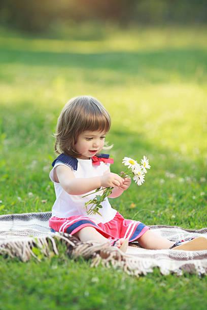kleines mädchen mit blumen - drees und sommer stock-fotos und bilder